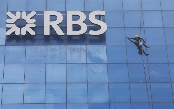 © Reuters. Worker cleans the glass exterior next to the logo of RBS (Royal Bank of Scotland) bank at a building in Gurugram