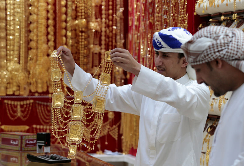 © Reuters. An employee shows a customer gold jewellery in a shop at the Gold Souq in Dubai