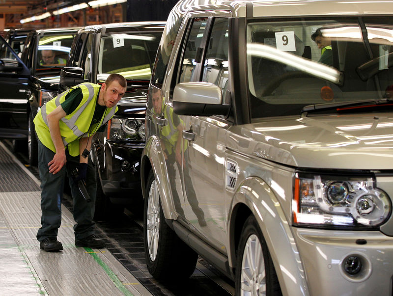 © Reuters. FILE PHOTO: A worker inspects a Land Rover Discovery on the production line at their factory in Solihull