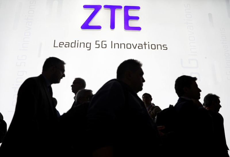 © Reuters. Visitors pass in front of the ZTE booth at the Mobile World Congress in Barcelona