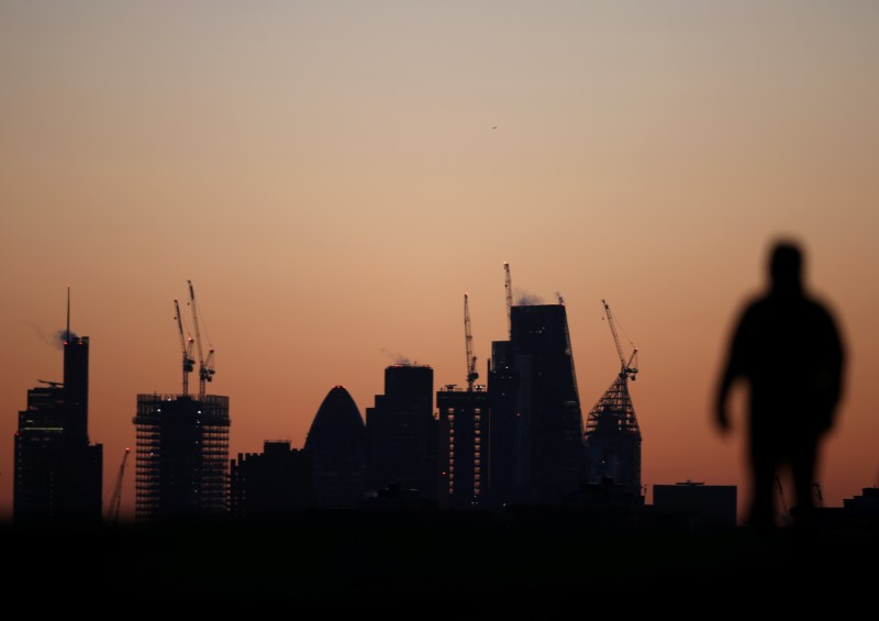 © Reuters. A man walks accross Primrose Hill as dawn breaks behind construction cranes in the City of London