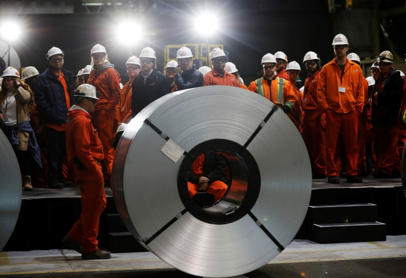 © Reuters. Workers stand behind rolls of steel at the ArcelorMittal Dofasco steel plant in Hamilton