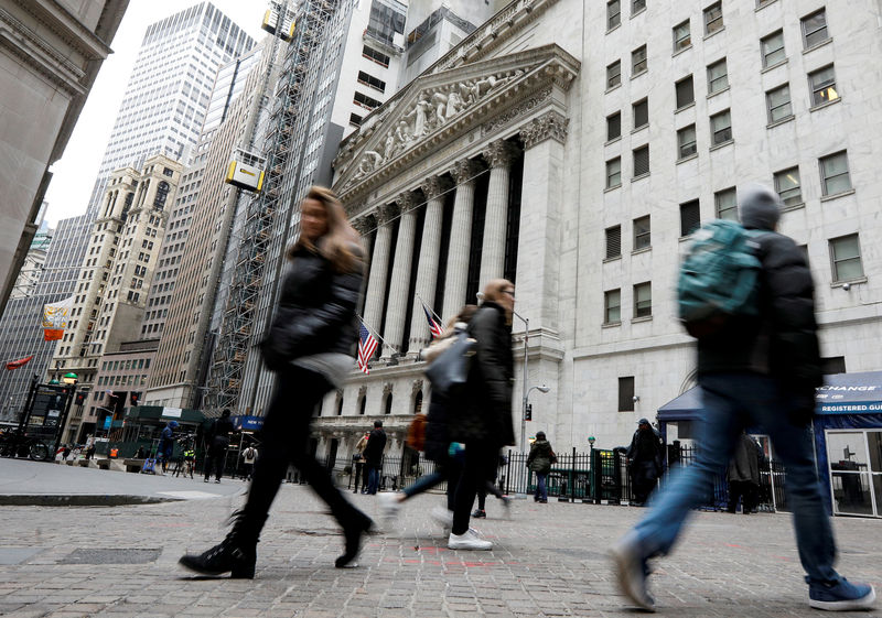 © Reuters. FILE PHOTO: People walk on Wall St. in front of the NYSE in New York