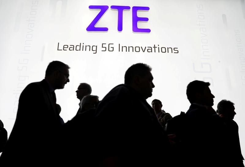 © Reuters. FILE PHOTO - Visitors pass in front of the ZTE booth at the Mobile World Congress in Barcelona