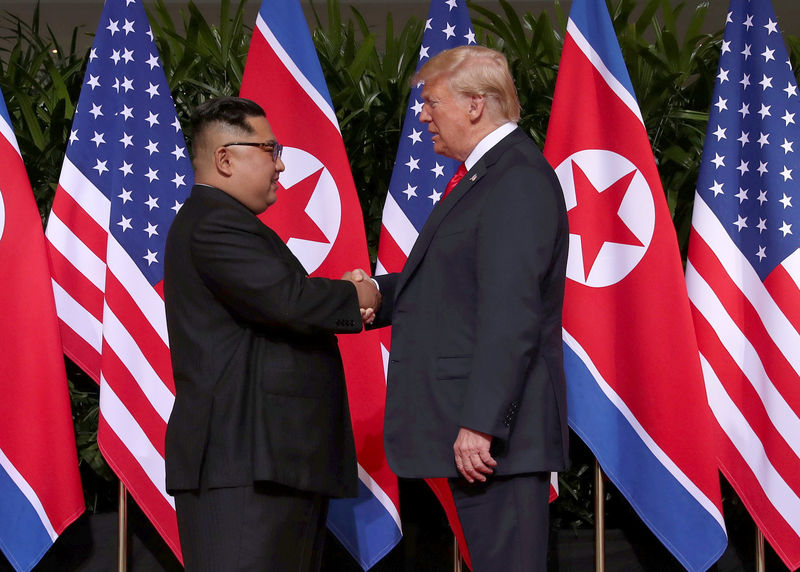 © Reuters. U.S. President Donald Trump and North Korea's leader Kim Jong Un shake hands after signing documents during a summit at the Capella Hotel on the resort island of Sentosa, Singapore