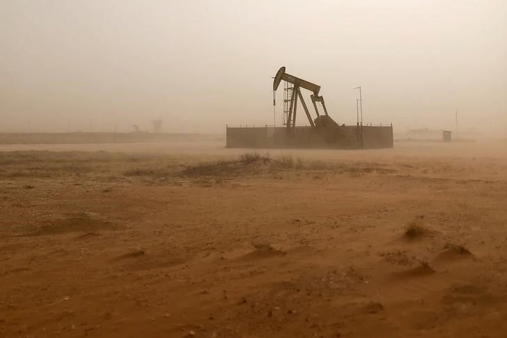 © Reuters. FILE PHOTO: Pump jack lifts oil out of well during sandstorm in Midland