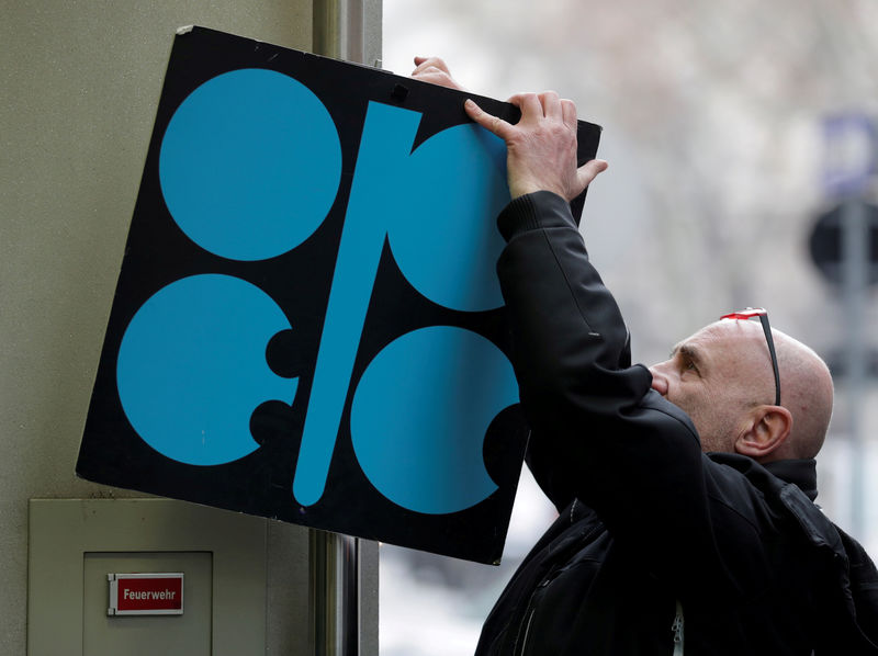 © Reuters. FILE PHOTO: A man fixes a sign with OPEC's logo next to its headquarter's entrance in Vienna