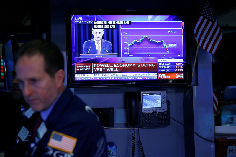 © Reuters. Traders work on the floor of the New York Stock Exchange (NYSE) as a TV screen shows the Fed Rate hike announcment in New York City