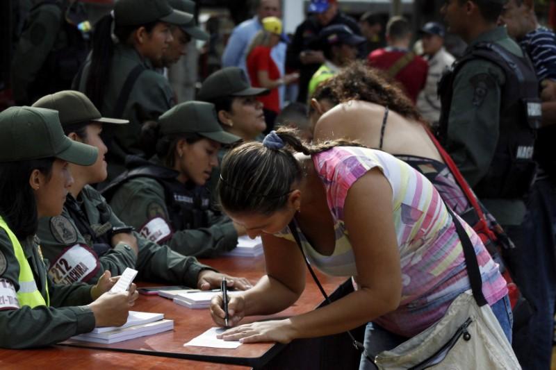 © Reuters. Mulher preenche formulário de imigração antes de passar a fonteira para a Colômbia em San Antonio del Tachira, Venezuela