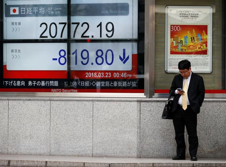 © Reuters. Man looks at a mobile phone next to an electronic board showing Japan's Nikkei average outside a brokerage in Tokyo