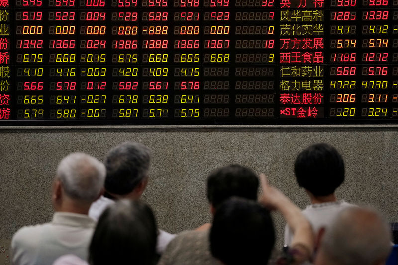 © Reuters. Investors look at an electronic board showing stock information at a brokerage house in Shanghai