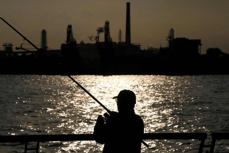 © Reuters. A man fishes near a factory at the Keihin industrial zone in Kawasaki, Japan