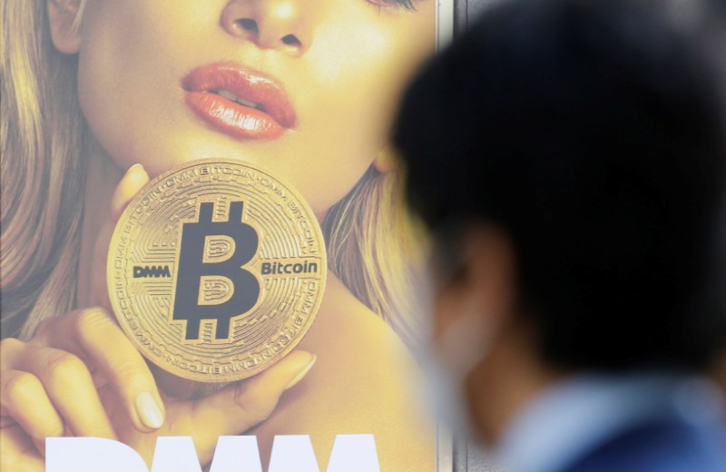 © Reuters. FILE PHOTO: A man stands near an advertisement of a cryptocurrency exchange in Tokyo