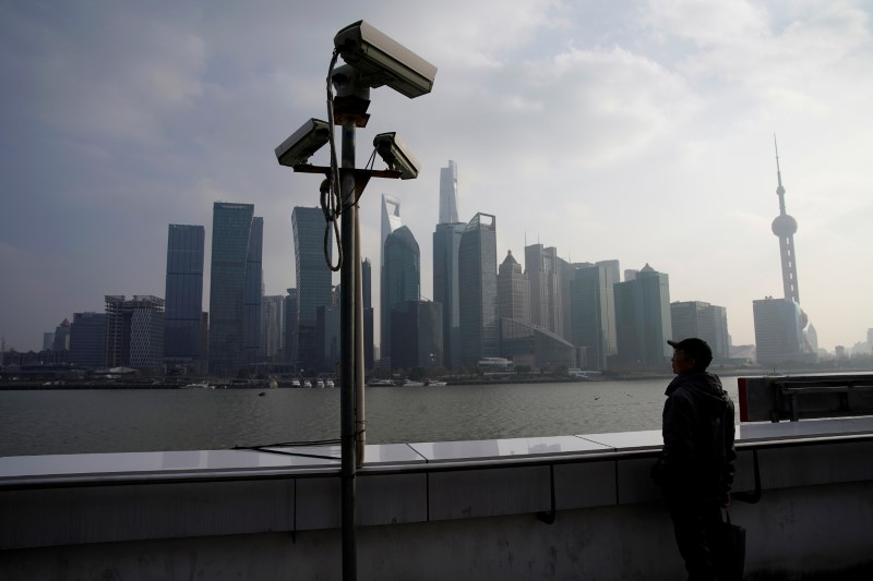 © Reuters. FILE PHOTO -  A man stands on the Bund in front of Shanghai's financial district of Pudong in Shanghai
