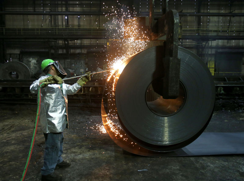 © Reuters. FILE PHOTO: A worker cuts a piece from a steel coil at the Novolipetsk Steel PAO steel mill in Farrell