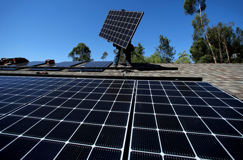 © Reuters. FILE PHOTO: A solar installer from installs a solar panel on the roof of a residential home in Scripps Ranch