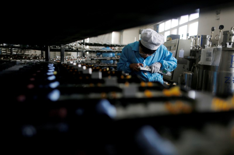 © Reuters. FILE PHOTO: Labourer works inside an electronics factory in Qingdao