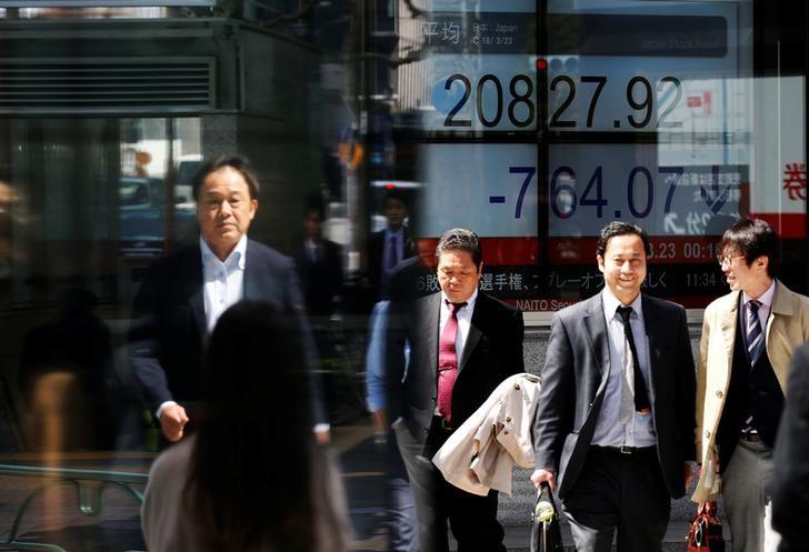 © Reuters. People walk past an electronic board showing Japan's Nikkei average outside a brokerage in Tokyo