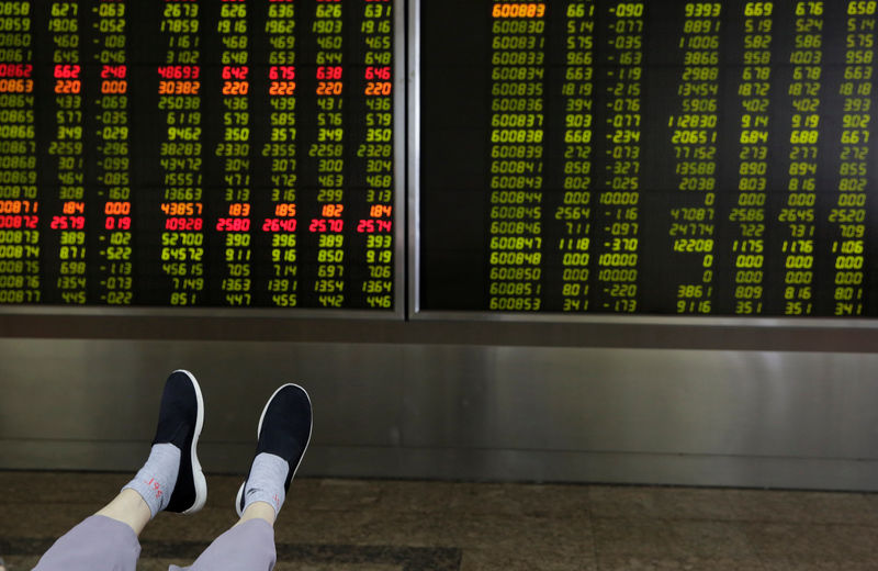 © Reuters. The feet of an investor are pictured as he looks at a board showing stock prices at a brokerage office in Beijing