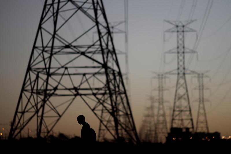 © Reuters. Homem passa por torres de energia em Brasília, Brasil