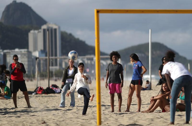 © Reuters. Malala joga futebol com meninas na praia de Copacabana no Rio de Janeiro