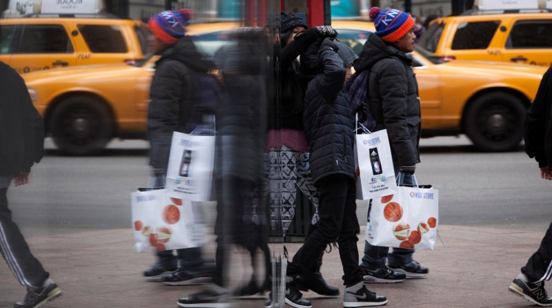 © Reuters. FILE PHOTO: People are reflected in a mirror as they shop in New York