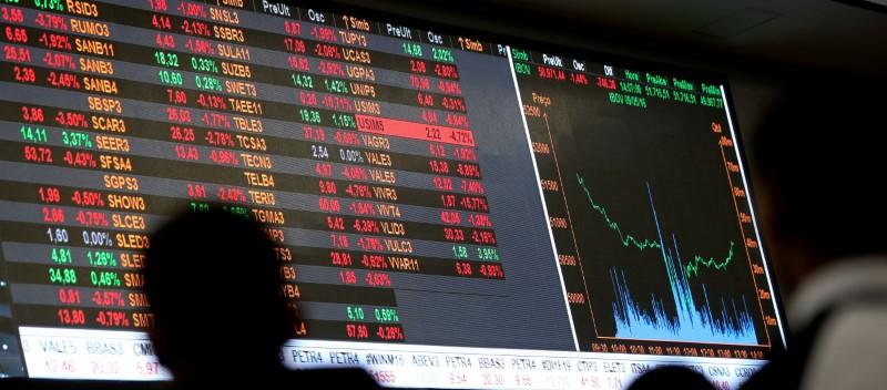 © Reuters. Pessoas observam painel com as cotações das ações na B3