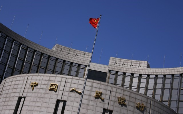 © Reuters. A Chinese national flag flutters outside the headquarters of the People's Bank of China in Beijing