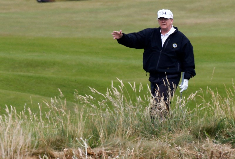 © Reuters. FILE PHOTO: U.S. President Donald Trump gestures as he walks on the course of his golf resort, in Turnberry