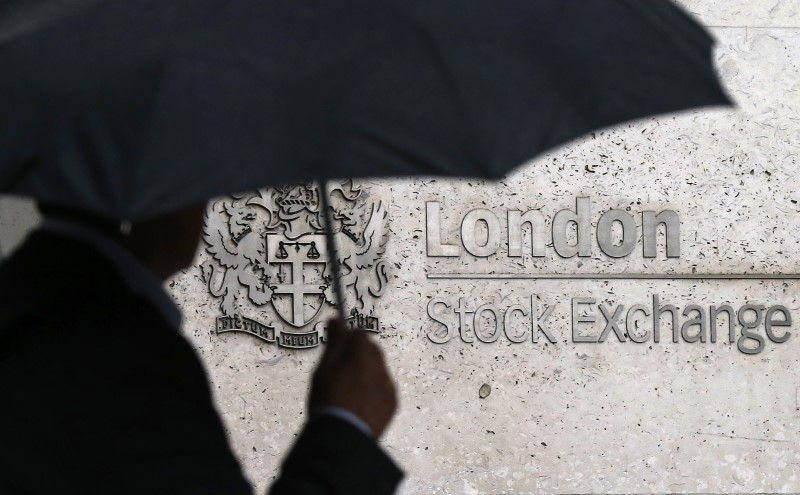 © Reuters. FILE PHOTO: A man shelters under an umbrella as he walks past the London Stock Exchange