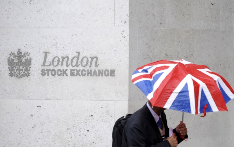 © Reuters. FILE PHOTO: A worker shelters from the rain as he passes the London Stock Exchange in London