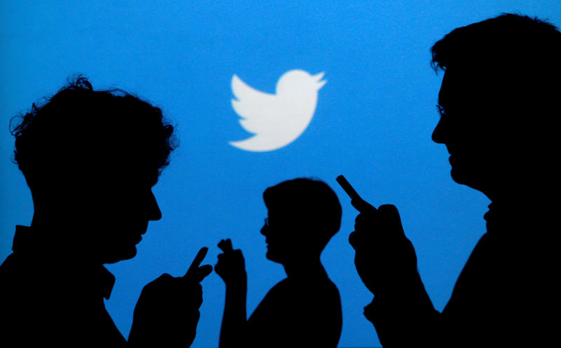 © Reuters. FILE PHOTO: People holding mobile phones are silhouetted against a backdrop projected with the Twitter logo