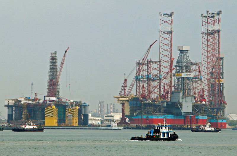 © Reuters. FILE PHOTO: Tugboats pass jack-up rigs at a Keppel FELS shipyard in Singapore