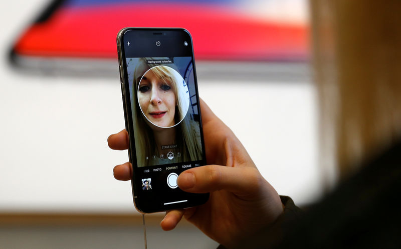 © Reuters. FILE PHOTO: A customer uses the new face-recognition software on the new iPhone X inside the Apple Store in Regents Street in London