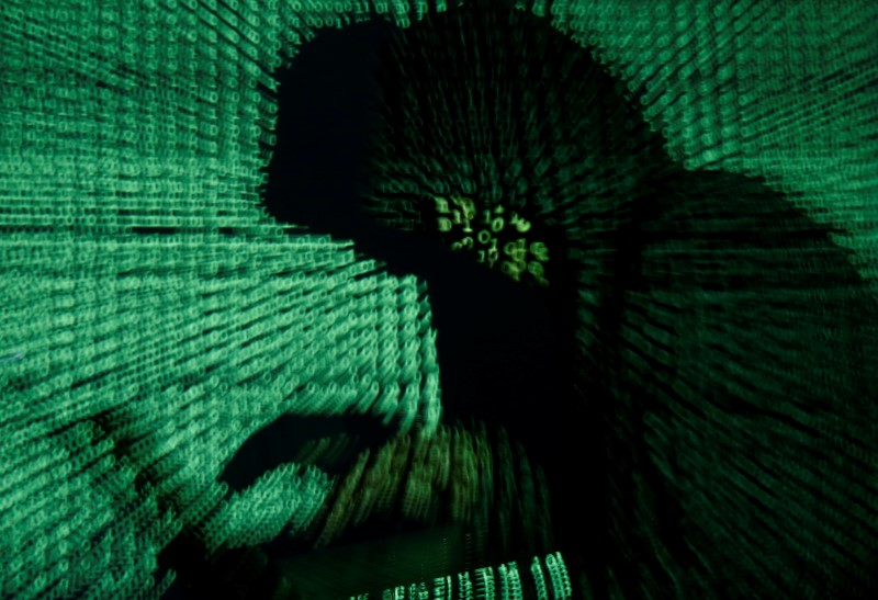 © Reuters. Man holds laptop computer as cyber code is projected on him in this illustration picture