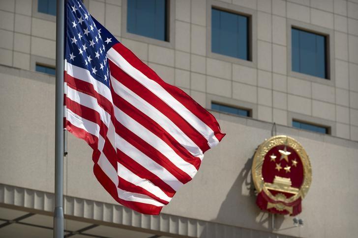 © Reuters. Флаг США на фоне герба Китая в Пекине