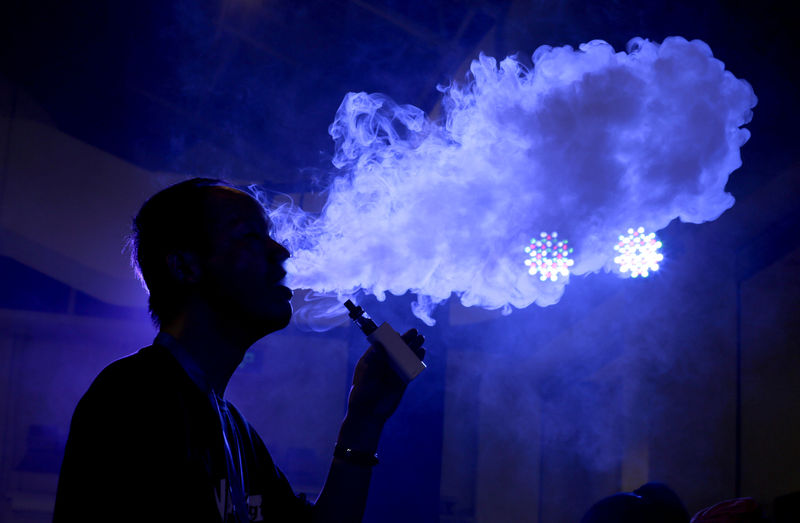 © Reuters. FILE PHOTO:    An exhibitor staff member uses an electronic cigarette at VAPE CHINA EXPO in Beijing