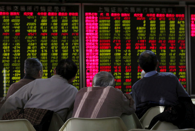 © Reuters. FILE PHOTO: Men look at an electronic board showing stock information at a brokerage house in Beijing