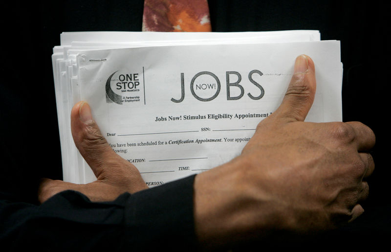 © Reuters. FILE PHOTO: Man carrying a stack of job listings listens to a discussion at the One Stop employment center in San Francisco