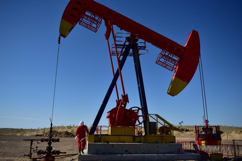 © Reuters. FILE PHOTO Worker inspects a pump jack at an oil field in Tacheng, Xinjiang