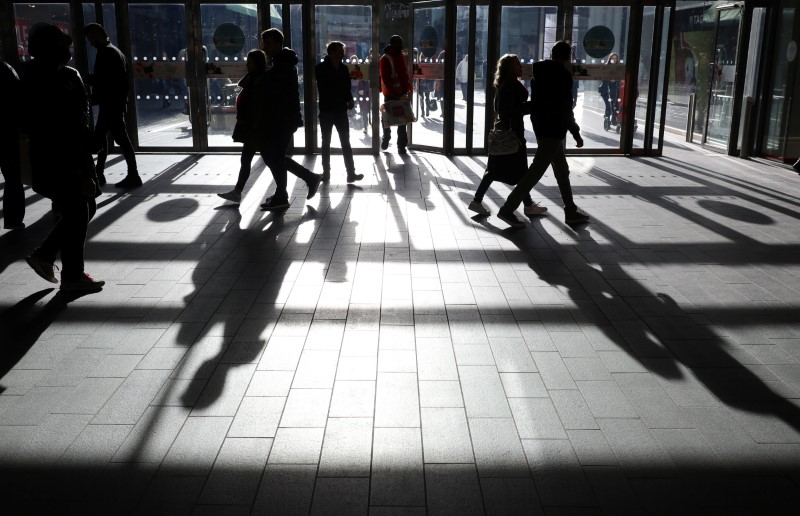 © Reuters. FILE PHOTO:  People's shadows are seen as shoppers are silhouetted in the bright sunshine at the Westfield shopping centre, Stratford, London