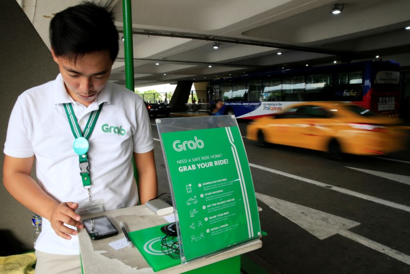 © Reuters. A Grab employee uses the Apps to book a cab for passengers at the Ninoy Aquino International Airport (NAIA) in the metro Manila