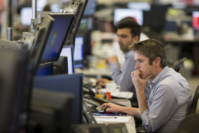 © Reuters. FILE PHOTO: Dealers work on the IG Group trading floor in London, Britain