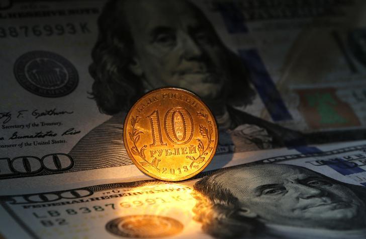 © Reuters. Десятирублевая монета на фоне стодолларовых купюр