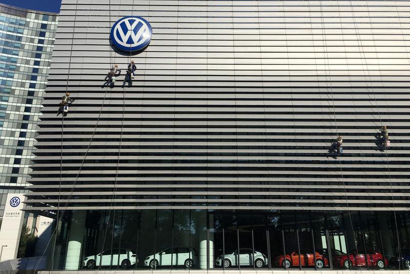 © Reuters. Workers clean the facade of a car showroom under a Volkswagen logo in Beijing