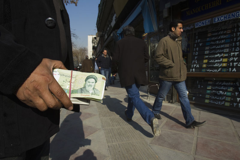 © Reuters. A money changer holds Iranian currency as he waits for customers in Tehran's business district