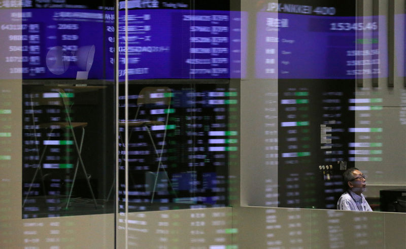 © Reuters. Market prices are reflected in a glass window at the TSE in Tokyo