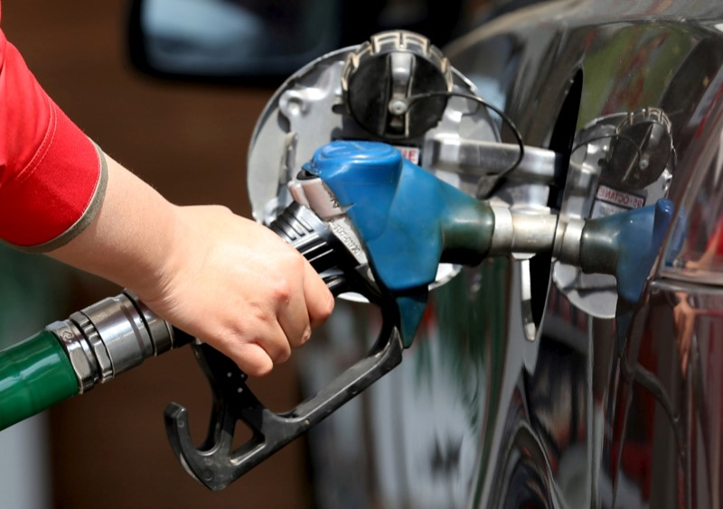 © Reuters. FILE PHOTO: A female employee fills the tank of a car at a petrol station in Cairo