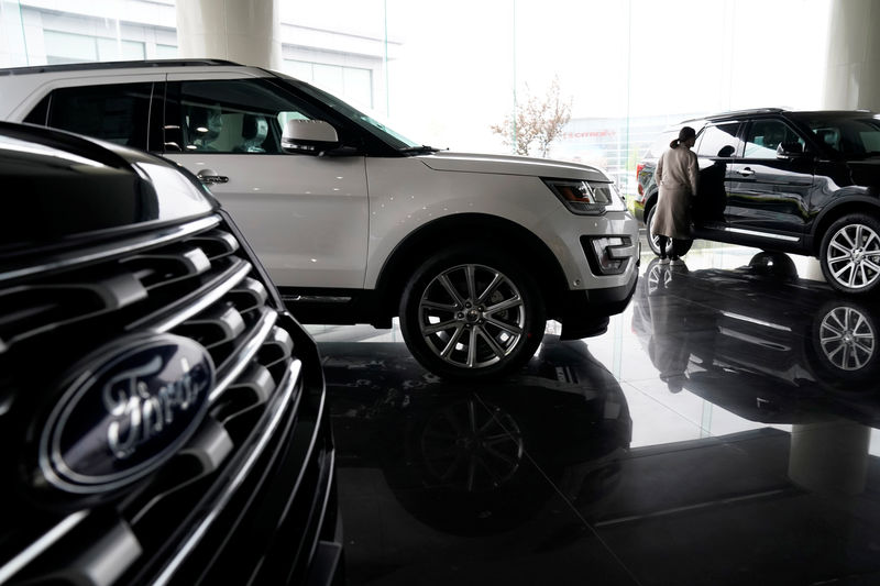 © Reuters. FILE PHOTO : A woman looks at Ford cars at a dealer shop in Shanghai