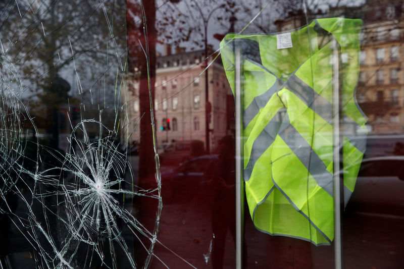 © Reuters. A yellow vest hangs inside a vandalized store front the morning after clashes with protesters wearing yellow vests, a symbol of a French drivers' protest against higher diesel taxes, in Paris